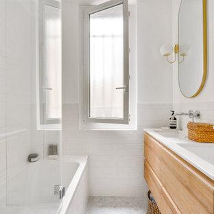 Exemple d'une salle d'eau scandinave avec un placard à porte plane, des portes de placard en bois brun, un combiné douche/baignoire, un carrelage blanc, un carrelage métro, un mur blanc, un lavabo encastré, un sol gris, un plan de toilette blanc, meuble double vasque et meuble-lavabo suspendu.