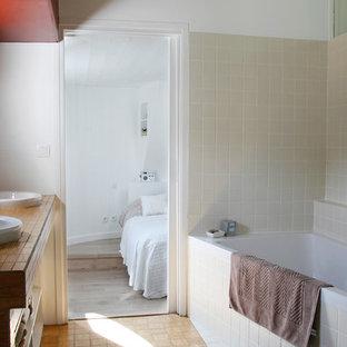 Modelo de cuarto de baño principal, actual, pequeño, con bañera esquinera, ducha a ras de suelo, baldosas y/o azulejos beige, baldosas y/o azulejos de cerámica, suelo de bambú y encimera de madera