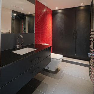 Inspiration för ett stort funkis svart svart badrum, med släta luckor, svarta skåp, en toalettstol med hel cisternkåpa, röd kakel, keramikplattor, klinkergolv i porslin, ett undermonterad handfat och grått golv