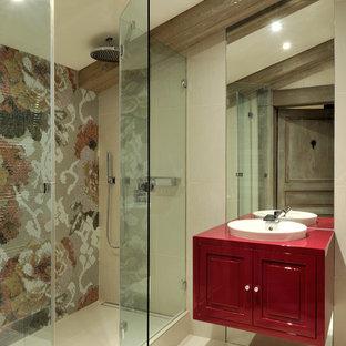 Aménagement d'une salle de bain contemporaine avec un lavabo posé, un placard avec porte à panneau encastré, des portes de placard rouges, un carrelage multicolore, carrelage en mosaïque et un mur beige.