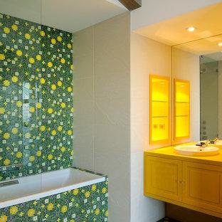Ispirazione per una stanza da bagno padronale contemporanea di medie dimensioni con ante con riquadro incassato, ante gialle, vasca da incasso, vasca/doccia, piastrelle multicolore, piastrelle a mosaico, pareti bianche, pavimento con piastrelle a mosaico e lavabo sottopiano