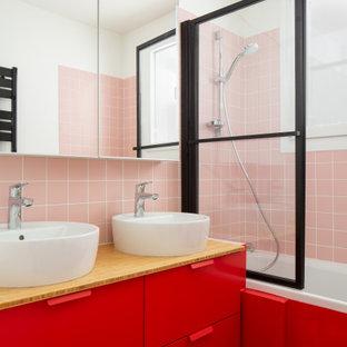 Idées déco pour une petit salle d'eau contemporaine avec un placard à porte plane, des portes de placard rouges, une baignoire en alcôve, un combiné douche/baignoire, un carrelage rose, un mur blanc, une vasque, un plan de toilette en bois, un sol rouge et un plan de toilette beige.
