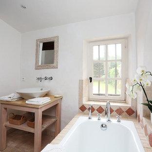 Cette image montre une douche en alcôve principale méditerranéenne avec un placard sans porte, des portes de placard en bois vieilli, une baignoire posée, un carrelage beige, un mur blanc, une vasque, un plan de toilette en bois et un sol beige.