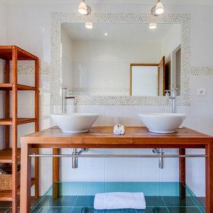 Réalisation d'une salle de bain principale design de taille moyenne avec une plaque de galets, un mur blanc, un sol en carrelage de céramique, une vasque, un placard sans porte, des portes de placard en bois brun, un carrelage blanc, un plan de toilette en bois et un plan de toilette marron.