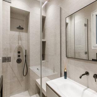 Aménagement d'une salle de bain contemporaine avec un carrelage beige, un mur beige, un lavabo intégré, une cabine de douche à porte battante et un plan de toilette blanc.