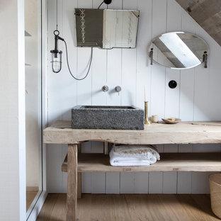 Inspiration pour une salle de bain rustique avec un placard sans porte, des portes de placard en bois clair, un mur blanc, un sol en bois clair, une vasque et un plan de toilette en bois.