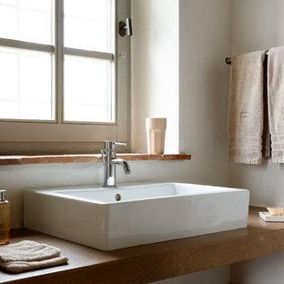 Immagine di una stanza da bagno mediterranea con pareti bianche, lavabo a bacinella e top marrone