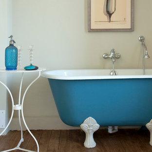 Exemple d'une salle de bain principale éclectique de taille moyenne avec une baignoire sur pieds, un combiné douche/baignoire, un mur beige et un sol en bois brun.