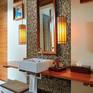 Réalisation d'une salle de bain design avec un lavabo suspendu et un plan de toilette en bois.