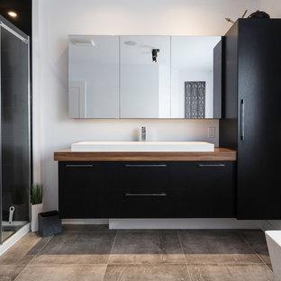 Foto di una stanza da bagno padronale minimal di medie dimensioni con ante lisce, ante nere, vasca giapponese, zona vasca/doccia separata, piastrelle nere, piastrelle in ceramica, pareti grigie, lavabo a bacinella, top in laminato, pavimento grigio e porta doccia scorrevole