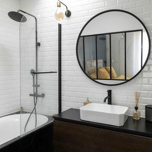 На фото: ванные комнаты в стиле лофт с плоскими фасадами, темными деревянными фасадами, ванной в нише, душем над ванной, белой плиткой, настольной раковиной, черным полом, открытым душем и черной столешницей