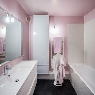 パリの中くらいのコンテンポラリースタイルのおしゃれな子供用バスルーム (フラットパネル扉のキャビネット、白いキャビネット、アンダーマウント型浴槽、シャワー付き浴槽、分離型トイレ、白いタイル、セラミックタイル、ピンクの壁、横長型シンク、珪岩の洗面台、グレーの床、オープンシャワー、白い洗面カウンター、洗面台1つ、フローティング洗面台) の写真