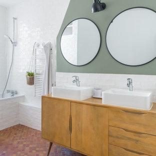 Bild på ett funkis badrum, med möbel-liknande, skåp i mellenmörkt trä, vit kakel, grå väggar, klinkergolv i terrakotta, ett fristående handfat, träbänkskiva och rött golv