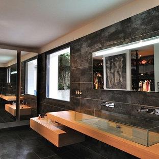 グルノーブルの広いコンテンポラリースタイルのおしゃれなバスルーム (浴槽なし) (黒いタイル、セラミックタイル、セラミックタイルの床、横長型シンク、木製洗面台、フラットパネル扉のキャビネット、淡色木目調キャビネット、バリアフリー、分離型トイレ、グレーの壁、グレーの床、オープンシャワー、ベージュのカウンター) の写真