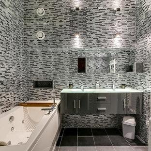 На фото: главная ванная комната среднего размера в современном стиле с серыми фасадами, полом из керамической плитки, монолитной раковиной, стеклянной столешницей, гидромассажной ванной, серой плиткой, черной плиткой и зеркальной плиткой с