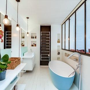 Réalisation d'une salle de bain principale nordique de taille moyenne avec des portes de placard blanches, une baignoire indépendante, un mur blanc, un sol en bois peint et une vasque.