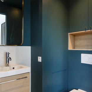 他の地域の中くらいの北欧スタイルのおしゃれなマスターバスルーム (フラットパネル扉のキャビネット、淡色木目調キャビネット、アルコーブ型シャワー、壁掛け式トイレ、白いタイル、磁器タイル、青い壁、テラゾーの床、壁付け型シンク、人工大理石カウンター、グレーの床、引戸のシャワー、白い洗面カウンター) の写真