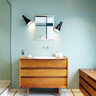 Aménagement d'une salle de bain principale contemporaine de taille moyenne avec des portes de placard en bois brun, un mur bleu, un lavabo posé, un plan de toilette en bois et un plan de toilette marron.