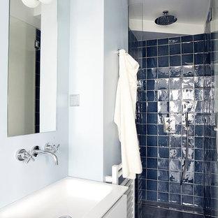 Cette image montre une petite salle de bain design avec un carrelage bleu, des carreaux de céramique, un mur bleu, des portes de placard blanches et un plan vasque.