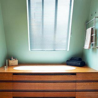 Cette photo montre une salle de bain principale tendance de taille moyenne avec une baignoire encastrée et un mur vert.