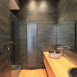 Foto de cuarto de baño con ducha, actual, de tamaño medio, con ducha empotrada, baldosas y/o azulejos negros, baldosas y/o azulejos de piedra, paredes negras, suelo de madera en tonos medios y lavabo sobreencimera