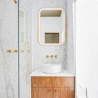 Réalisation d'une salle d'eau design avec un placard à porte plane, des portes de placard en bois brun, un carrelage blanc, des dalles de pierre, un mur blanc, une vasque et un plan de toilette blanc.