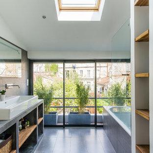 Ejemplo de cuarto de baño principal, nórdico, con lavabo de seno grande, armarios abiertos, encimera de cemento, bañera encastrada, paredes blancas y suelo de pizarra