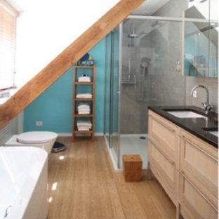 Foto de cuarto de baño con ducha, contemporáneo, pequeño, con armarios tipo vitrina, bañera exenta, ducha empotrada, sanitario de una pieza, baldosas y/o azulejos blancos, baldosas y/o azulejos de cerámica, paredes azules, suelo de bambú, lavabo integrado y encimera de granito