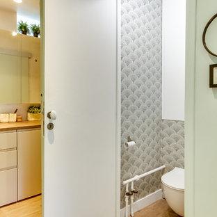 Réalisation d'une salle de bain design avec un placard à porte plane, des portes de placard blanches, un WC suspendu, un mur blanc, un lavabo posé, un sol marron, un plan de toilette marron et des toilettes cachées.
