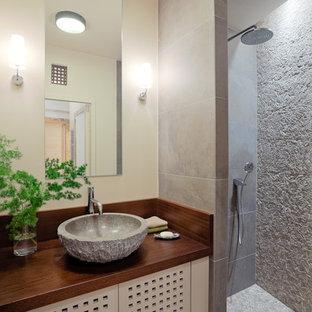 Inredning av ett asiatiskt litet brun brunt badrum med dusch, med en kantlös dusch, beige kakel, beige väggar, ett fristående handfat och träbänkskiva