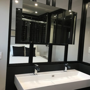 Small trendy 3/4 black tile and subway tile plywood floor and brown floor bathroom photo in Toulouse with beaded inset cabinets, black cabinets, a wall-mount toilet, gray walls, a trough sink, marble countertops and white countertops