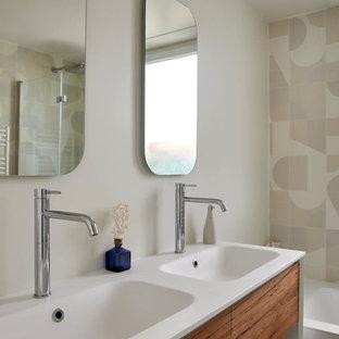 Aménagement d'une salle de bain contemporaine avec un placard à porte plane, des portes de placard en bois brun, un carrelage multicolore, un mur blanc, un lavabo intégré et un plan de toilette blanc.