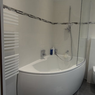Small traditional bathroom in Paris with beaded cabinets, grey cabinets, a corner bath, a wall mounted toilet, grey tiles, terracotta tiles, white walls, ceramic flooring, a built-in sink and glass worktops.