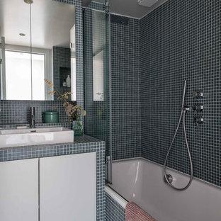 Ispirazione per una piccola stanza da bagno padronale minimal con ante a filo, ante blu, vasca sottopiano, piastrelle blu, piastrelle di vetro, pareti blu, pavimento con piastrelle a mosaico, lavabo da incasso, top piastrellato, pavimento blu e top blu