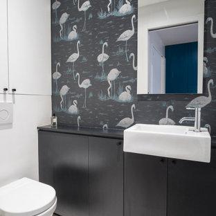Réalisation d'une salle d'eau design de taille moyenne avec un placard à porte plane, des portes de placard noires, un WC suspendu, un mur multicolore, un sol en carrelage de porcelaine, un lavabo posé, un sol gris, un plan de toilette noir, meuble simple vasque, meuble-lavabo encastré et du papier peint.