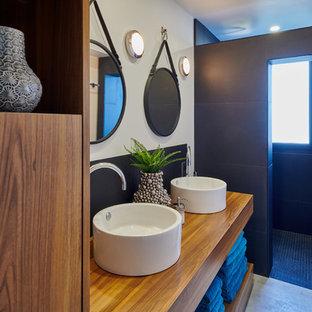 Свежая идея для дизайна: ванная комната среднего размера в стиле фьюжн с коричневыми фасадами, открытым душем, белой плиткой, черной плиткой, плиткой из сланца, белыми стенами, бетонным полом, настольной раковиной, столешницей из дерева, серым полом, открытым душем и коричневой столешницей - отличное фото интерьера