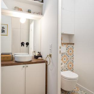Idées déco pour une salle de bain contemporaine avec un placard à porte plane, des portes de placard blanches, un carrelage multicolore, des carreaux de béton, un mur blanc, un sol en bois brun, une vasque, un plan de toilette en bois, un sol marron, un plan de toilette marron, des toilettes cachées, meuble simple vasque et meuble-lavabo encastré.