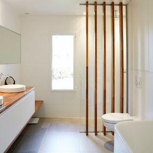 Стильный дизайн: маленькая главная ванная комната в современном стиле с накладной раковиной, фасадами с декоративным кантом, белыми фасадами, столешницей из дерева, накладной ванной, инсталляцией, керамической плиткой, белыми стенами, полом из керамической плитки, открытым душем, белой плиткой, серым полом и открытым душем - последний тренд
