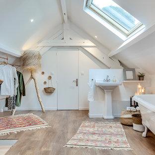 Idée de décoration pour une salle d'eau champêtre de taille moyenne avec une baignoire sur pieds, un mur blanc, un lavabo de ferme, un sol marron et un sol en bois clair.