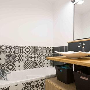Ispirazione per una piccola stanza da bagno minimal con vasca sottopiano, pistrelle in bianco e nero, piastrelle di cemento, pareti bianche, pavimento in legno massello medio e lavabo a bacinella