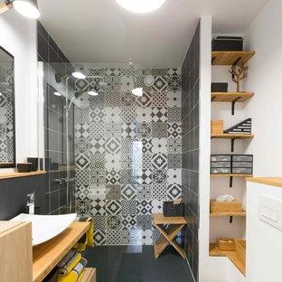 Idéer för att renovera ett mellanstort funkis brun brunt badrum med dusch, med en vägghängd toalettstol, svart och vit kakel, cementkakel, vita väggar, ett fristående handfat, släta luckor, skåp i ljust trä, träbänkskiva, en dusch i en alkov, ljust trägolv och med dusch som är öppen
