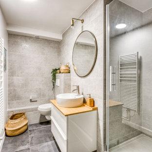 Modern inredning av ett litet orange oranget badrum för barn, med en dusch i en alkov, en vägghängd toalettstol, grå kakel, keramikplattor, grå väggar, klinkergolv i keramik, ett undermonterad handfat, träbänkskiva, grått golv, dusch med gångjärnsdörr, släta luckor och vita skåp