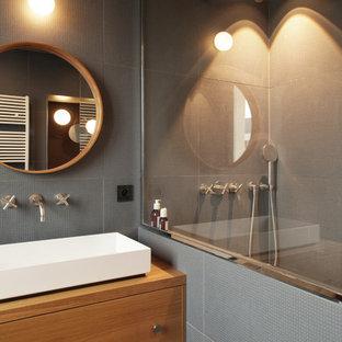 Cette image montre une petite salle de bain design avec des portes de placard en bois brun, un carrelage gris, des carreaux de céramique, un mur gris, une grande vasque, un plan de toilette en bois, aucune cabine et un plan de toilette marron.