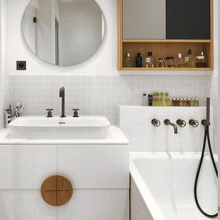 Inspiration pour une salle de bain design avec un placard à porte plane, des portes de placard blanches, un carrelage gris, un mur blanc, une vasque et un plan de toilette blanc.