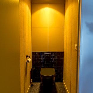 Esempio di una piccola stanza da bagno padronale design con ante a filo, ante gialle, doccia a filo pavimento, WC sospeso, piastrelle nere, pareti gialle, pavimento in vinile, lavabo integrato, pavimento nero e porta doccia scorrevole