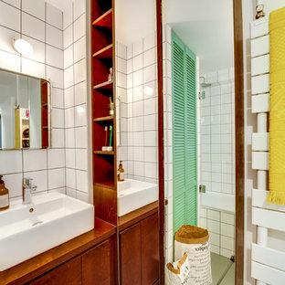 Exemple d'une salle d'eau chic de taille moyenne avec une baignoire en alcôve, un combiné douche/baignoire, un carrelage blanc, des carreaux de céramique, un mur blanc, une vasque, des portes de placard en bois brun et un plan de toilette en bois.