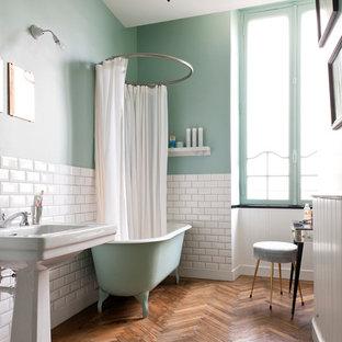 Modelo de cuarto de baño principal, actual, de tamaño medio, con lavabo con pedestal, baldosas y/o azulejos blancos, baldosas y/o azulejos de cemento, bañera con patas, paredes verdes y suelo de madera oscura