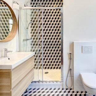 Exemple d'une grande douche en alcôve principale tendance avec un WC suspendu, un carrelage noir et blanc, des carreaux de béton, un mur blanc, un sol en carrelage de céramique, un lavabo suspendu et des portes de placard en bois clair.