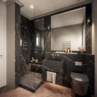 Réalisation d'une salle d'eau design de taille moyenne avec un WC suspendu, un carrelage noir, du carrelage en marbre, un lavabo intégré, un plan de toilette en marbre, un sol marron, aucune cabine, un plan de toilette noir, des portes de placard noires, une douche d'angle, un mur gris et un sol en carrelage de céramique.