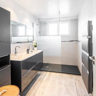 Cette image montre une petit salle de bain design avec un placard à porte plane, des portes de placard grises, un carrelage blanc, un mur blanc, un plan vasque, un sol beige, aucune cabine et un plan de toilette blanc.